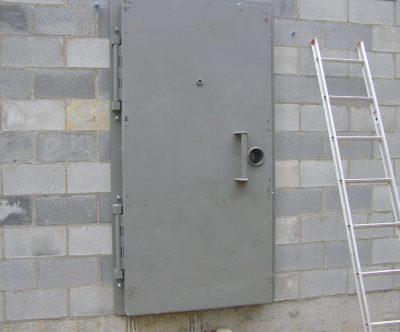 Blast door mounted on a safe room wall